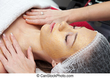 Receiving a cleansing therapy - Young woman having a face...