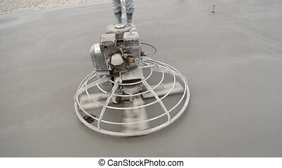 Worker smoothes concrete surface a special device