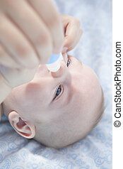 Mother using baby nasal aspirator. She is doing a mucus...