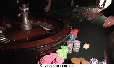 People playing roulette - Casino croupier dealer moving...