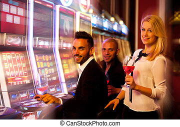 three young people playing slot machines in casino - young...