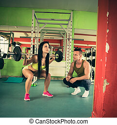 Personal fitness coach trains beautiful woman in gym