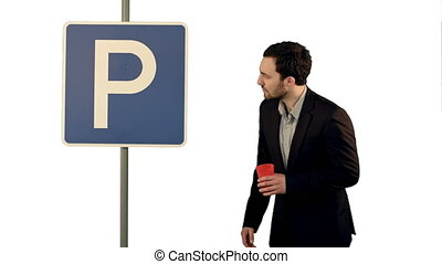 Man with cup of tea near parking sign on white background isolated