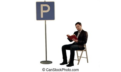 Young man reading a book near parking sign on white...