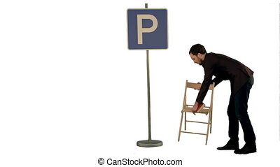 Businessman reading a book near parking sign on white...