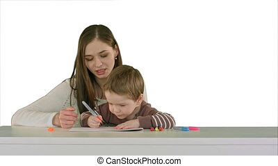 Mom and kid boy painting together on table on white background isolated