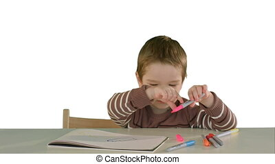 A son drawing at the table at home on white background isolated