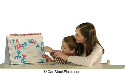 Mother and son make word Mama on the desk on white background isolated