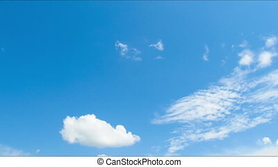 Clouds moving across the blue sky.