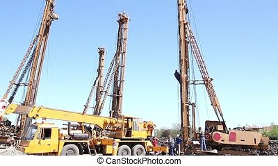 Drilling machines towers. - Worker is climbing over ladders...