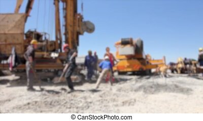 Action at the construction site. - Workers with shovels are...