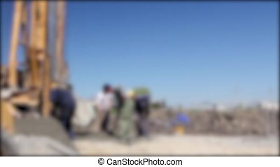 Blurred view construction site - Workers with shovels are...