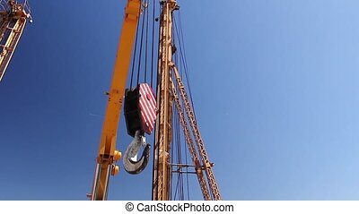 Mobile crane - Crane hook is moving across blue sky at...