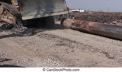 Excavator is moving on dusty ground - Caterpillar is...