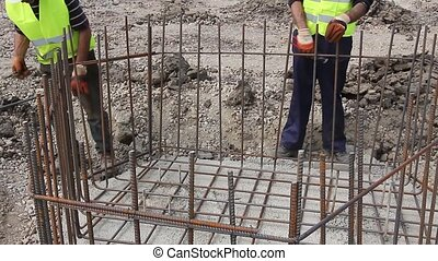 Rebar tying - Workers are placing the rebar making a newly...