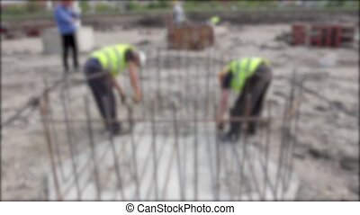 Rebar tying - Blurred view on workers until they are placing...