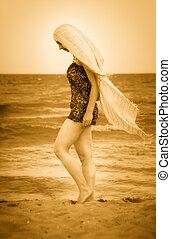Woman with veil on peaceful sunny beach