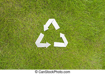 Paper recycle symbol on green grass