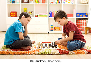 Let me show you a move - kids playing chess sitting on the...