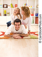 Happy family having fun together on the floor in the kids...