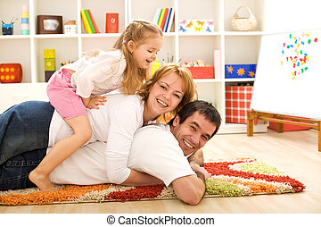 Happy family heap - parents and a kid having fun