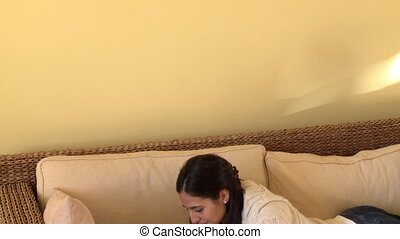 Attractive woman lying down on sofa using a laptop at home