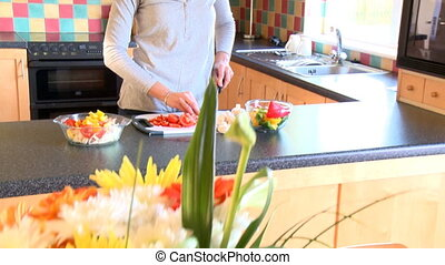 Smiling woman preparing salad in the kitchen