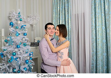 Nice love couple sitting on carpet in front of fireplace