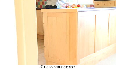 Brunette woman rinsing vegetables in the kitchen