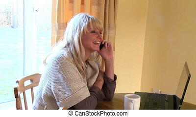 Smiling woman on phone using a laptop at home