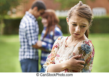 Lonely Jealous Teenage Girl With Romantic Couple In...
