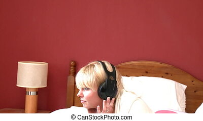 Peaceful woman listening music lying down on bed at home