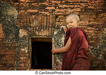 Buddhist novice monk - Young novice monk standing outside...