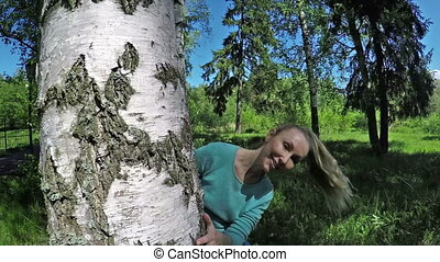 The beautiful woman with a smile looks out from birch and waves hair. Slow motion.