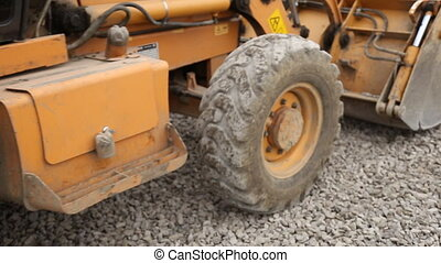 bulldozer spreads gravel on the territory of a close-up