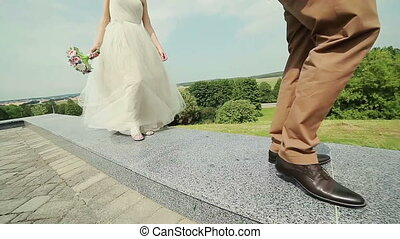 Bride and groom walking on the curb. Wide angle