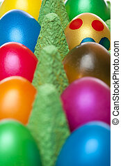 Closeup of colourful Easter eggs in egg box. Only one egg...