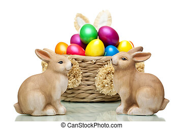 Two Easter bunnies sitting in front of basket full of colourful Easter  eggs. Isolated on white background.