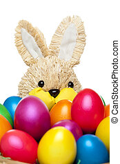 Easter bunny has basket full of colourful easter eggs.