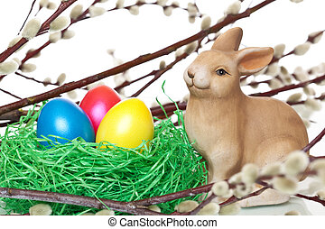 cute Easter bunny sitting beside Easter nest with Easter eggs