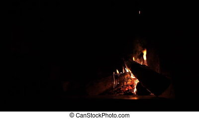 Wood burning in a fireplace on dark