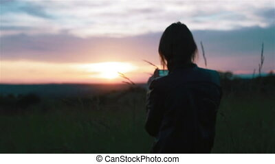 Young woman takes sunset pictures