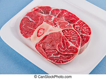 Two fresh veal shank meat on white plate, top view