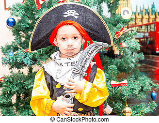 Little boy child dressed as pirate for Halloween  on background of Christmas tree