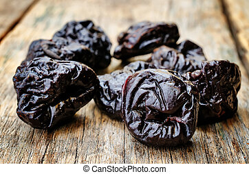 prunes on a dark wood background tinting selective focus