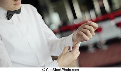 Man puts cufflinks on sleeves - Man wearing bow tie puts...