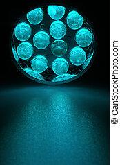 LEDs - 12 cyan LEDs shine on a surface.