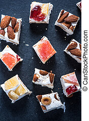 Italian nougat bars cut in pieces on dark slate background