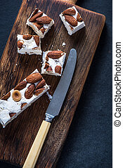 Traditional italina nougat with almonds on wooden rustic...