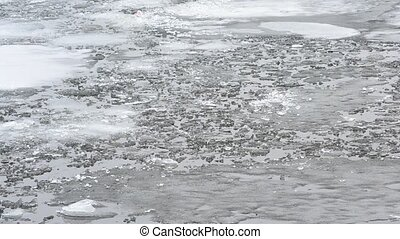 Blocks of melting ice floating on water surface with waves -...
